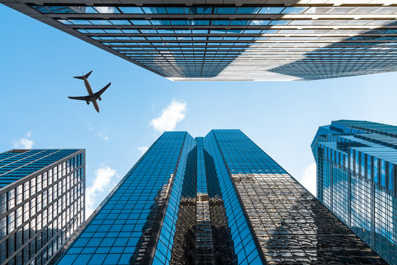 Airplane flying over office buildings 00818